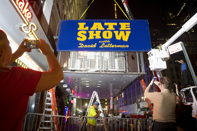 "People take photos as workers remove marquee from Ed Sullivan Theater where ""The Late Show"" with David Letterman used to tape in Manhattan borough New York"
